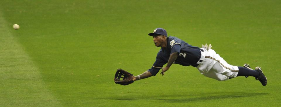 Milwaukee Brewers center fielder Nyjer Morgan can't come up with a ball hit by St. Louis Cardinals' Edwin Jackson during the third inning of Game 2 of baseball's National League championship series Monday, Oct. 10, 2011, in Milwaukee. (AP Photo/Jim Prisching)