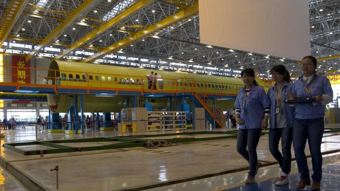 Employees walk past as China's home-grown airliner C919 is seen during it's final assembly in Shanghai
