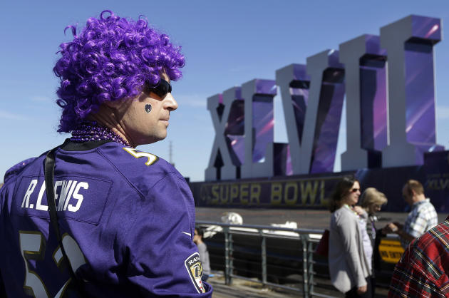 Baltimore Ravens fan Cal Wheaton looks out toward the Super Bowl XLVII sculpture on a barge along the Riverwalk in New Orleans, Sunday, Feb. 3, 2013. The city hosts NFL football's Super Bowl XLVII