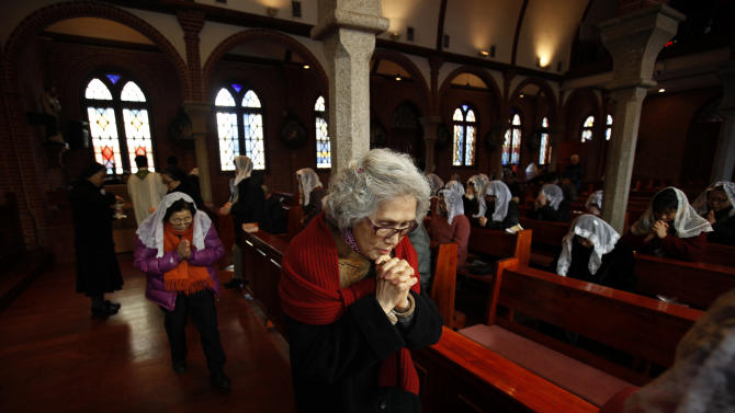 A woman prays during a mass at a catholic church in Seoul