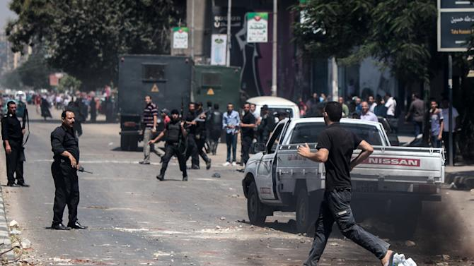 Civilians runs across a street in Cairo as policemen gather during clashes with Muslim Brotherhood supporters following a rally marking the first anniversary of a brutal Cairo crackdown, on August 14, 2014