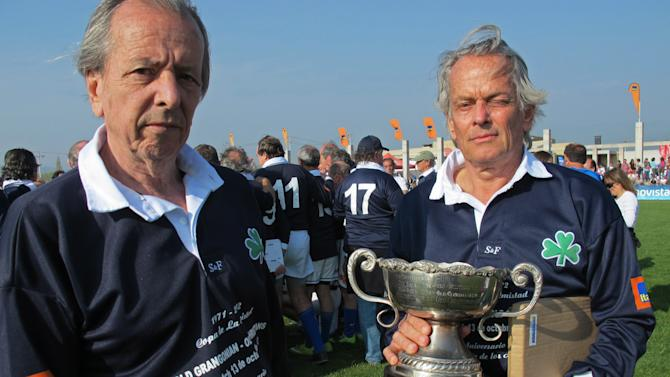 Former members of Uruguay's rugby team Daniel Fernandez, 66, left, and Eduardo Strauch, 65, hold a commemorative trophy during a rugby game with Chile's former players as they mark the 40th anniversary of their plane crash in Santiago, Chile, Saturday, Oct. 13, 2012. The rugby players marked the 40 year anniversary since they survived 72 days in the Chilean Andes after their plane crashed in 1972. Only 16 of the 45 passengers aboard survived, by feeding on dead passengers preserved in the snow. (AP Photo/Luis Andres Henao)