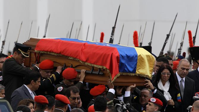 The coffin containing the remains of Venezuela's late President Hugo Chavez is carried from the military academy, at the start of a procession to the military museum, his final resting place, in Caracas, Venezuela, Friday, March 15, 2013. Venezuelans lined up to bid their last farewell to Hugo Chavez on Friday. Chavez was 58 when he died of an undisclosed type of cancer on March 5. (AP Photo/Fernando Llano)