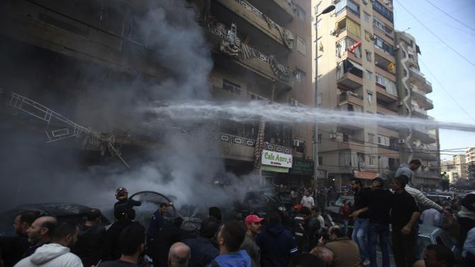 Firefighters extinguish a fire from a building at the site of an explosion in the Haret Hreik area, in the southern suburbs of the Lebanese capital Beirut