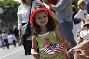A girl wears a junior firefighting hat during Santa …