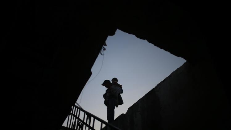 Palestinian boy carries his sister atop the roof of their family's house in the northern Gaza Strip