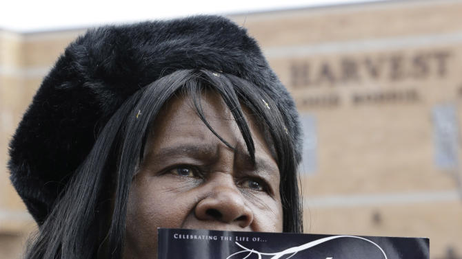 A mourner holds up a program for the funeral of Hadiya Pendleton, outside the Greater Harvest Missionary Baptist Church during the funeral service of Hadiya Pendleton Saturday, Feb. 9, 2013, in Chicago. Hundreds of mourners and dignitaries including first lady Michelle Obama packed the funeral service Saturday for a Chicago teen whose killing catapulted her into the nation's debate over gun violence. (AP Photo/Nam Y. Huh)