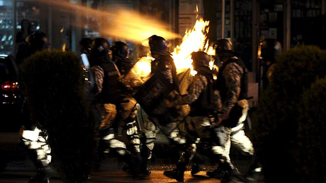 Police storm towards protestors in front of the Macedonian government building in Skopje
