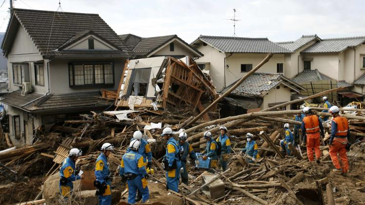 Fire-fighters and police officers search for survivors at a site where a landslide swept through a residential area at Asaminami ward in Hiroshima