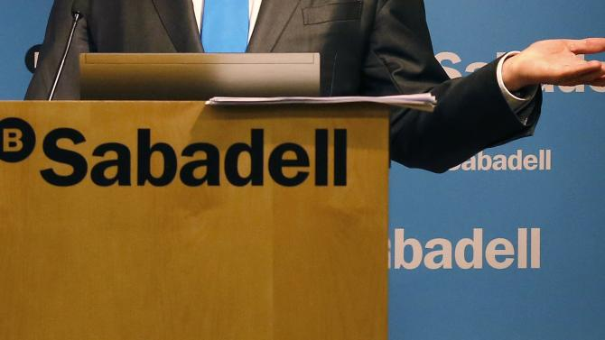Banc Sabadell's Chairman Josep Oliu shows a dossier of the company's 2014 results during a news conference at its headquarters in central Barcelona