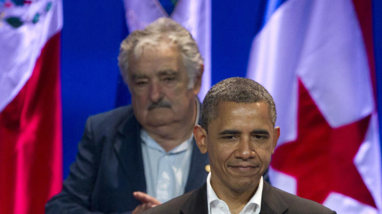 President Barack Obama applauds as Colombian singer Shakira arrives, below, as Uruguay's President Jose Mujica stands behind during the arrival ceremony at the sixth Summit of the Americas in Cartagena, Colombia, Saturday April 14, 2012. (AP Photo/Carolyn Kaster)