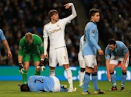 Micah Richards, bottom left, suffered the knee injury against Swansea on Saturday