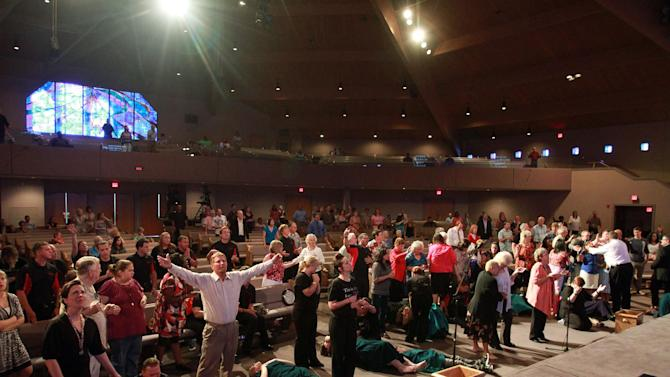 In this March 25, 2012, photo, Brownsville Assembly senior pastor Rev. Evon Horton, far right, performs the practice of the laying of hands on members of the congregation in Pensacola, Fla. The church that was home to the largest Pentecostal outpouring in U.S. history is on the edge of financial ruin. The revival that drew some 5,500 people nightly at its height saddled the congregation with an $11.5 million debt that members were left to pay off after both the out-of-town throngs and former Rev. John Kilpatrick moved on. The red ink is mostly unknown outside the congregation. (AP Photo/John David Mercer)