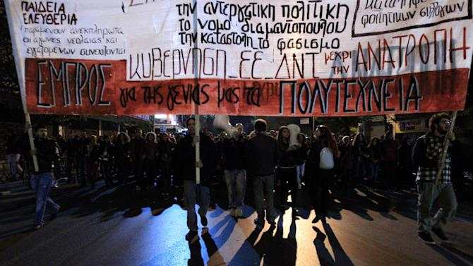 """Protesters march during a protest commemorating the student uprising against a military dictatorship in 1973, at the northern city of Thessaloniki  Greece, Sat. Nov. 17 2012. The banner is reading """"Against Government - IMF - EU. In the northern Greek city of Thessaloniki, Greece's second-largest city, about 12,000 people marched, police said. Some burned a European Union flag, angry over EU demands to cut Greek spending in order to get a desperately needed bailout loan. (AP Photo/Nikolas Giakoumidis)"""