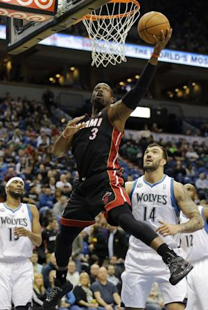 Miami Heat guard Dwyane Wade (3) goes up to shoot over Minnesota Timberwolves center Nikola Pekovic (14), of Montenegro, and forward Corey Brewer (13) during the first quarter of an NBA basketball game in Minneapolis, Saturday, Dec. 7, 2013. (AP Photo/Ann Heisenfelt)