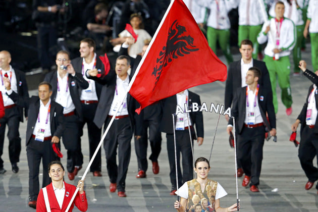 Albania's flag bearer Romela Begaj holds the national flag as he leads the contingent in the athletes parade during the opening ceremony of the London 2012 Olympic Games