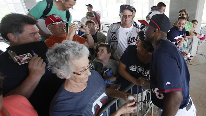 Minnesota Twins' Torii Hunter, right, poses for a photo with a fan as he signs autographs at the end of a workout at baseball spring training in Fort Myers, Fla., Tuesday March 3, 2015. (AP Photo/Tony Gutierrez)