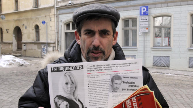 In this Wednesday Feb. 1, 2012 photo Vladimir Linderman, co-chairman of the Mother Tongue movement and a leader of Latvia's Russian community, holds a leaflet in downtown Riga, Latvia. On Saturday Feb. 17, 2011, Latvia will hold a referendum on whether Russian, the native language for about one-third of Latvia's 2.1 million residents, should become the country's second national language. (AP Photo/Roman Koksarov)
