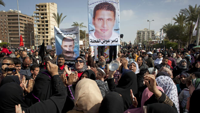 FILE - In this Friday, Feb. 22, 2013 file photo, Egyptian protesters chant anti-President Mohammed Morsi slogans and carry posters with pictures of victims of recent violence and their names in Port Said, Egypt. Egypt's streets have turned into a daily forum for airing a range of social discontents from labor conditions to fuel shortages and the casualties of myriad clashes over the past two years. Newly called parliamentary elections hold out little hope for plucking the country out of the turmoil and if anything, are likely to just fuel unrest and push it toward economic collapse. (AP Photo/Nasser Nasser, File)