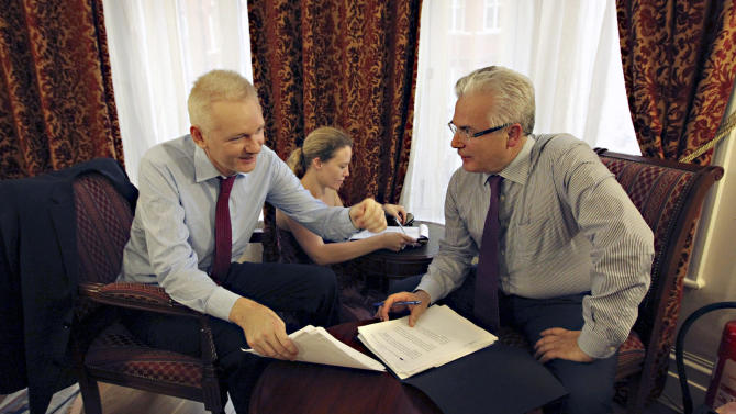WikiLeaks founder Julian Assange, left, talks with his legal adviser Balthasar Garcon, right, while they sit inside the Ecuadorian embassy in London, Sunday Aug. 19, 2012.  WikiLeaks founder Julian Assange took refuge inside Ecuador's Embassy in London two months ago, seeking to avoid extradition to Sweden for questioning over sexual misconduct allegations. (AP Photo / Sean Dempsey, PA) UNITED KINGDOM OUT - NO SALES - NO ARCHIVE