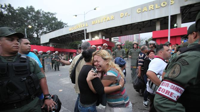 Supporters of Venezuela's President Hugo Chavez embrace outside the military hospital after learning that Chavez has died through an announcement by Venezuela's vice president in Caracas, Venezuela, Tuesday, March 5, 2013. Venezuela's Vice President Nicolas Maduro announced that Chavez died on Tuesday at age 58 after a nearly two-year bout with cancer. During more than 14 years in office, Chavez routinely challenged the status quo at home and internationally. He polarized Venezuelans with his confrontational and domineering style, yet was also a masterful communicator and strategist who tapped into Venezuelan nationalism to win broad support, particularly among the poor. (AP Photo/Fernando Llano)