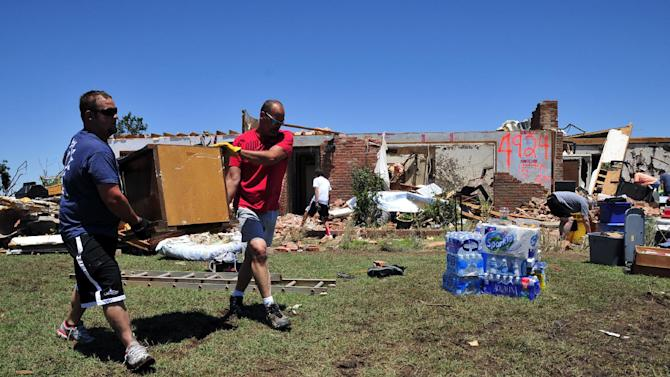 Josh Stapleton, left, and Dan Garrett help to salvage furniture from their friends Fred and Joann Horn's home that was destroyed by the tornado Saturday, June 1, 2013 in El Reno Okla. (AP Photo/Nick Oxford)