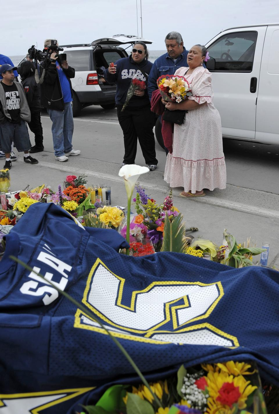 "Family members of former NFL star Junior Seau put flowers at memorial in the driveway of his home, Thursday, May 3, 2012, in Oceanside, Calif. Seau's apparent suicide stunned an entire city and saddened former teammates who recalled the former NFL star's ferocious tackles and habit of calling everybody around him ""Buddy."" (AP Photo/Denis Poroy)"