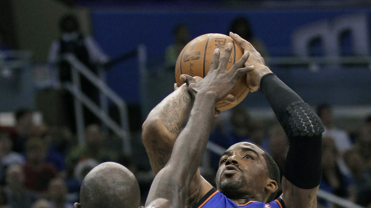 New York Knicks' J.R. Smith (8) shoots over Orlando Magic's Jason Richardson (23) during the first half of an NBA basketball game, Thursday, April 5, 2012, in Orlando, Fla. (AP Photo/John Raoux)