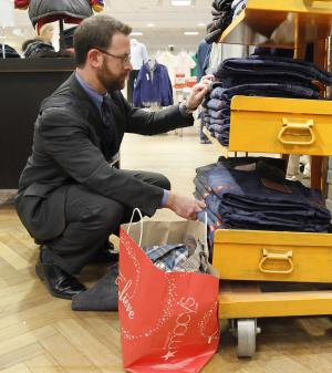 FILE - In this Dec. 13, 2011 file photo, Brad Cheskes of Chicago, shops at the Macy's on State Street store in Chicago.  Retail sales barely rose in December, but the gain was enough to push sales to a record level for 2011. It was the largest annual increase in more than a decade. (AP Photo/Charles Rex Arbogast, File)