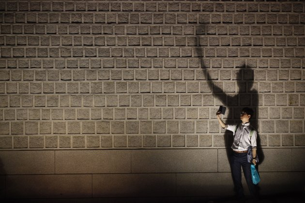 A man takes a photograph during the evening in front of a wall of Gyeongbok palace in central Seoul