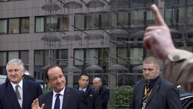 French President Francois Hollande, second left, looks at a journalist who puts up his finger to ask a question during arrivals for an EU summit in Brussels on Friday, Nov. 23, 2012. The prospect of failure hangs over a European Union leaders' summit intended to lay out the 27-country bloc's long-term spending plans. While heavyweights like Britain and France are pulling in opposite directions, smaller members are threatening to veto a deal to make themselves heard. (AP Photo/Virginia Mayo)