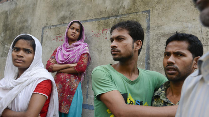 Workers stand outside an 11-story building that houses the Tung Hai Sweater Ltd. factory and apartments after a fire in Dhaka, Bangladesh, Thursday, May 9, 2013.  The fire broke out in the building Wednesday night, not long after the up to 300 workers of the factory went home for the day, killing at least eight people officials said Thursday. (AP Photo/Ismail Ferdous)