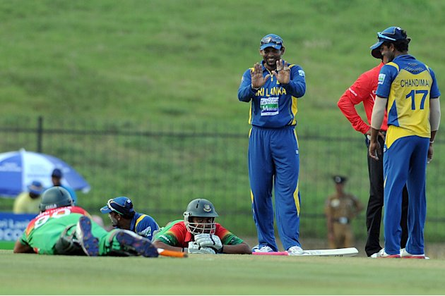 Sri Lankan cricketer Tillakaratne Dilshan (C) teases Bangladeshi batsmen Mahmudullah and Tamim Iqbal as they lie on the ground after wasps invaded the field during the opening one-day international (O