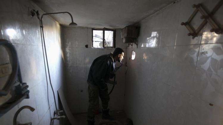 Free Syrian Army fighter holds weapon as he looks through a hole in wall in Deir al-Zor, eastern Syria