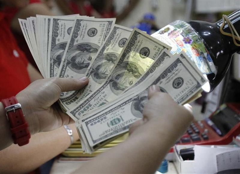 A worker counts U.S. dollar bills, which are being exchanged for Philippine Pesos, inside a money changer in Manila April 1, 2013. REUTERS/Romeo Ranoco/Files