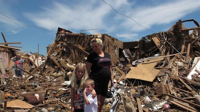In this Wednesday, May 22, 2013 photo, Leslie Paul stands with her children Hayden, 4, and Addison, 7, in the wreckage of their home in Moore, Okla. Paul, who is eight-months pregnant, went out as Monday's tornado approached to get her daughter from a school in the tornado's path. (AP Photo/Allen Breed)