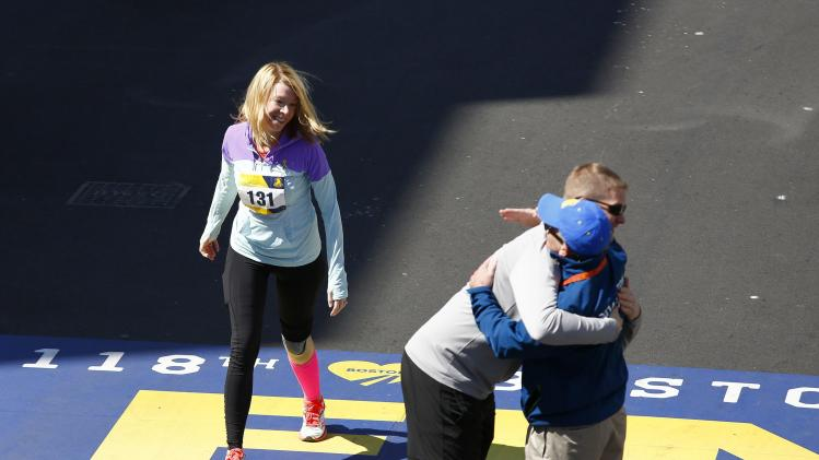 Haslet-Davis crosses the finish line while her husband hugs a supporter during a tribute run in Boston