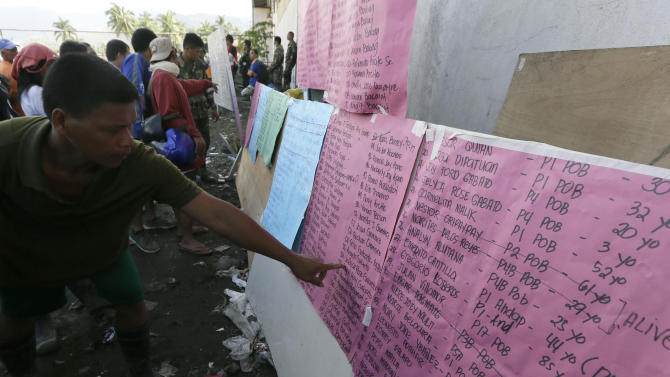 A resident checks the names of his missing relatives following Tuesday's storm in New Bataan township, Compostela Valley in the southern Philippines, Thursday, Dec. 6, 2012.  The powerful typhoon that washed away emergency shelters, a military camp and possibly entire families in the southern Philippines has killed hundreds of people with nearly 400 missing, authorities said Thursday. (AP Photo/Bullit Marquez)