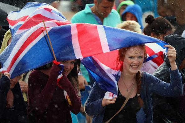 Members of the public shelter from the rain at the Olympic Park on Day 2 of the London 2012 Olympic Games on July 29, 2012 in London, England. (Photo by Jeff J Mitchell/Getty Images)