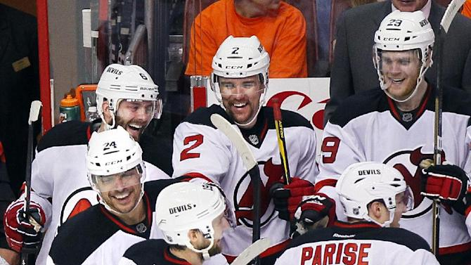 New Jersey Devils' Bryce Salvador (24) left, is surrounded by celebrating teammates after he scored an empty-net goal during the third period in Game 2 of an NHL hockey Stanley Cup second-round playoff series with the Philadelphia Flyers, Tuesday, May 1, 2012, in Philadelphia. The Devils won 4-1 evening the best of seven series at 1-1.(AP Photo/Tom Mihalek)
