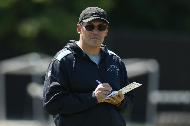 "This May 16, 2014, file photo, shows Carolina Panthers head coach Ron Rivera looking on at his players during an NFL football rookie minicamp in Charlotte, N.C. Rivera and quarterback Cam Newton seem more focused on the big picture: getting the Panthers to the playoffs in back-to-back seasons for the first time, and winning a postseason game for the first time since 2005. ""Status quo isn't good enough,"" Rivera said"