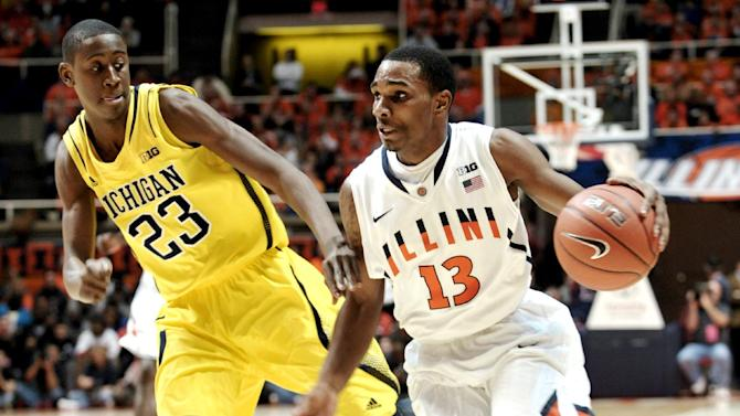 Illinois' Tracy Abrams (13) drives around Michigan's Caris LeVert (23) during the first half of an NCAA college basketball game, Sunday, Jan. 27, 2013, in Champaign, Ill. (AP Photo/John Dixon)