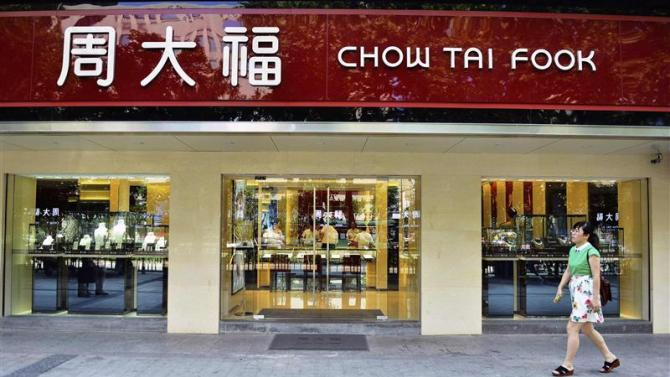 A woman walks past a Chow Tai Fook store in Hangzhou