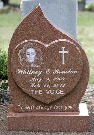 This Tuesday July 23, 2013 photo shows the new headstone at the grave of singer Whitney Houston, at Fairview Cemetery in Westfield, N.J., about 20 miles west of New York. The 48-year-old pop music queen died Feb. 11, 2012, in Beverly Hills, Calif. An autopsy found she had drowned accidentally, with heart disease and cocaine use contributing to her death. She is buried next to her father. (AP Photo/Julio Cortez)