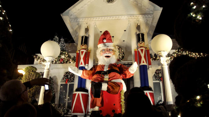 """This Dec. 4, 2012 photo shows spectators viewing a a giant Santa Claus at a decorated home in the Brooklyn borough of New York. Each holiday season, tour operator Tony Muia takes tourists from around the world on his """"Christmas Lights & Cannoli Tour"""" visiting the Brooklyn neighborhoods of Dyker Heights and Bay Ridge, where locals take pride in over-the-top holiday light displays.  (AP Photo/Seth Wenig)"""