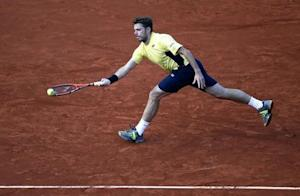 Stanislas Wawrinka of Switzerland returns a forehand to Guillermo Garcia-Lopez of Spain during their men's singles match at the French Open tennis tournament at the Roland Garros stadium in Paris