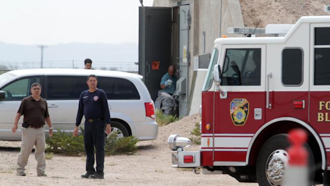 Firefighters and other workers work on the site of a former nuclear weapons bunker where Army investigators have detected radiation Tuesday, July 16, 2013 at Fort Bliss, Texas. Officials said Tuesday investigators are determining whether people on the west Texas post have been exposed. Post leaders said contaminated residue was buried in the 1950s and 1960s, when the base was operated by the Air Force. (AP Photo/The El Paso Times, Vanessa Monsisvais) EL DIARIO OUT; JUAREZ MEXICO OUT