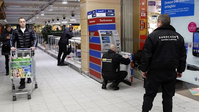 Bank staff fill a cash machine with euro currency in Vilnius, Lithuania, Tuesday. Dec. 30, 2014, as preparations continue for the currency swap-over.  Political leaders are hoping that joining the euro on Jan. 1 will help Lithuania distance itself further from Russian influence and reduce government borrowing costs. (AP Photo/Mindaugas Kulbis)