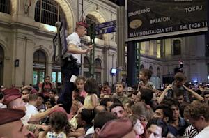 A policeman tries to control migrants as ticket control…