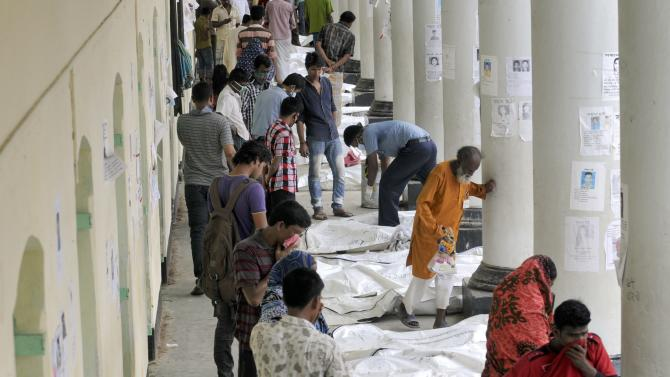 Bangladeshis look for their missing relatives along a row of dead bodies laid out near the site of a garment factory building that collapsed in Savar near Dhaka, Bangladesh, Wednesday May 8, 2013. Dozens of bodies recovered Wednesday from the building were so decomposed they were being sent to a lab for DNA identification, police said, as the death toll from Bangladesh's worst industrial disaster topped 800. (AP Photo/Ismail Ferdous)